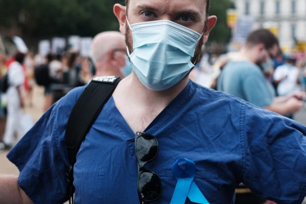 boy in blue polo shirt wearing white face mask