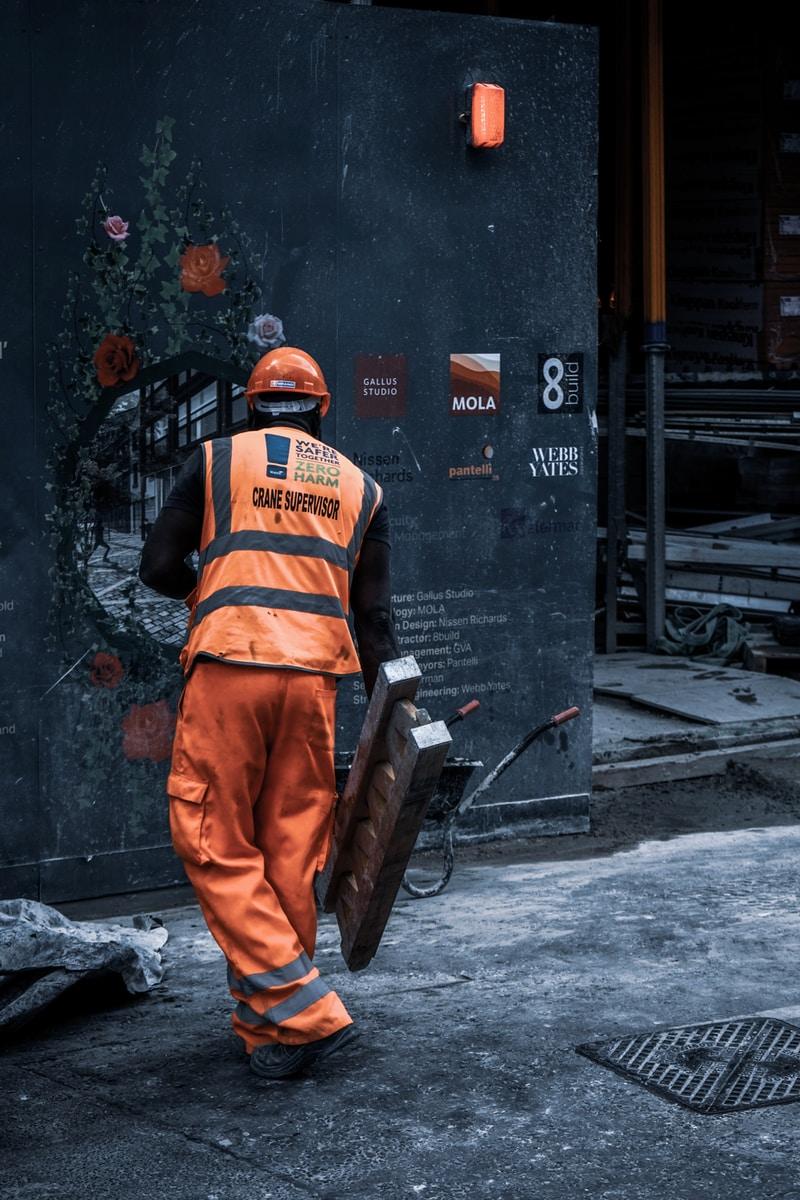 man in orange safety vest holding metal